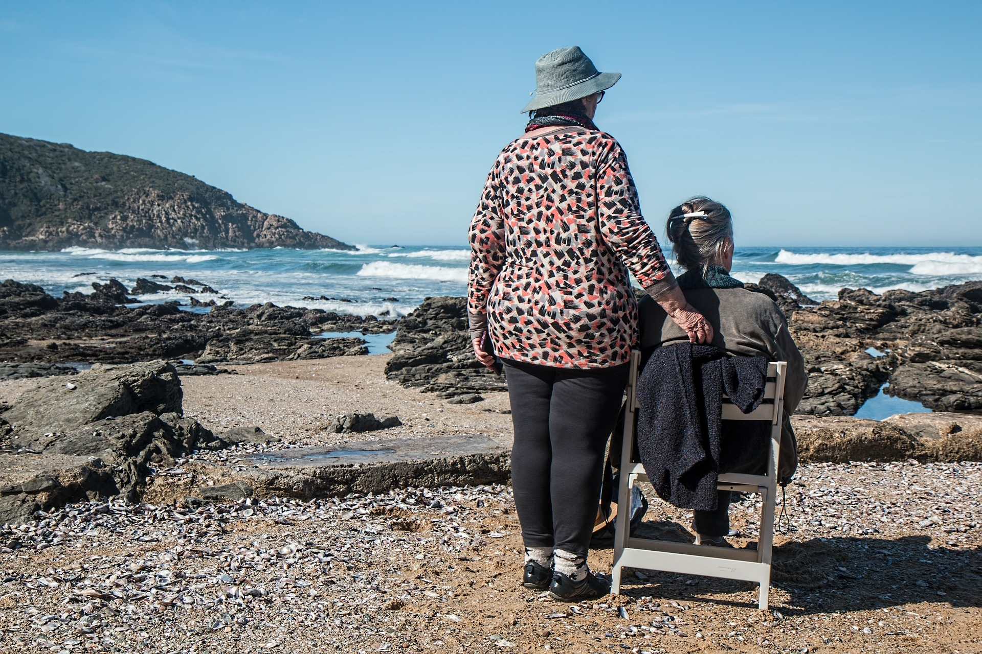 Lady sitting down on wooden chair looking out to sea, with other lady placing her right hand on the chair