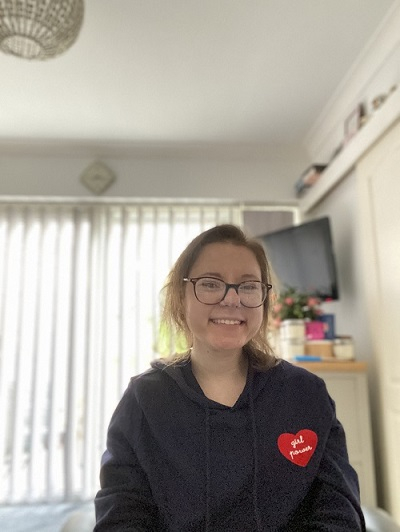 Danielle with a broad smile on her face wearing a hoodie with a love heart on