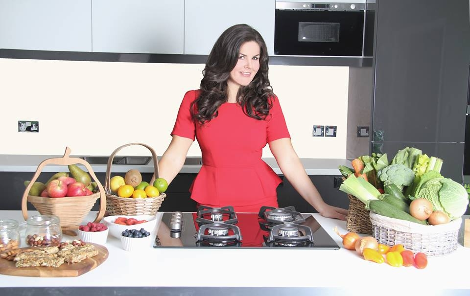 Lady in red dress standing behind kitchen counter full of fruit and vegetables