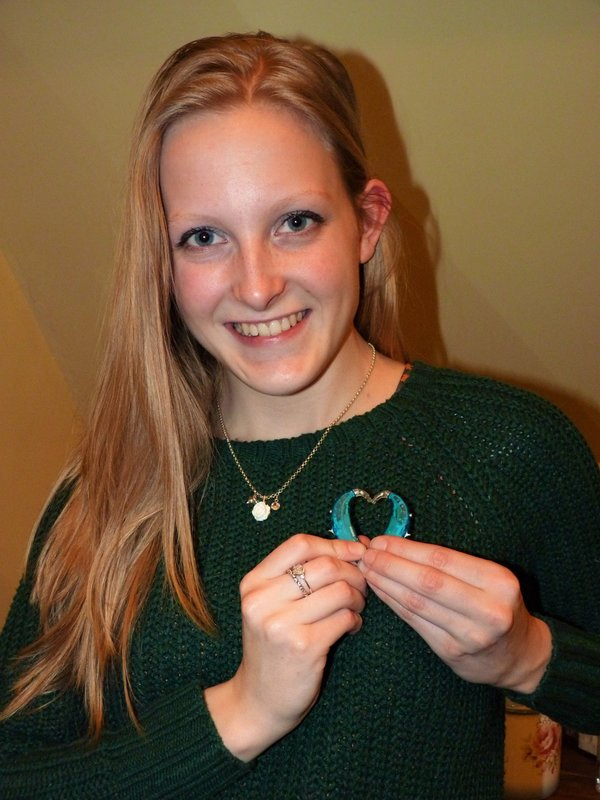 portrait photo of blonde haired girl wearing a green knitted jumper, smiling and holding up green and gold hearing aid accessories in the shape of a heart