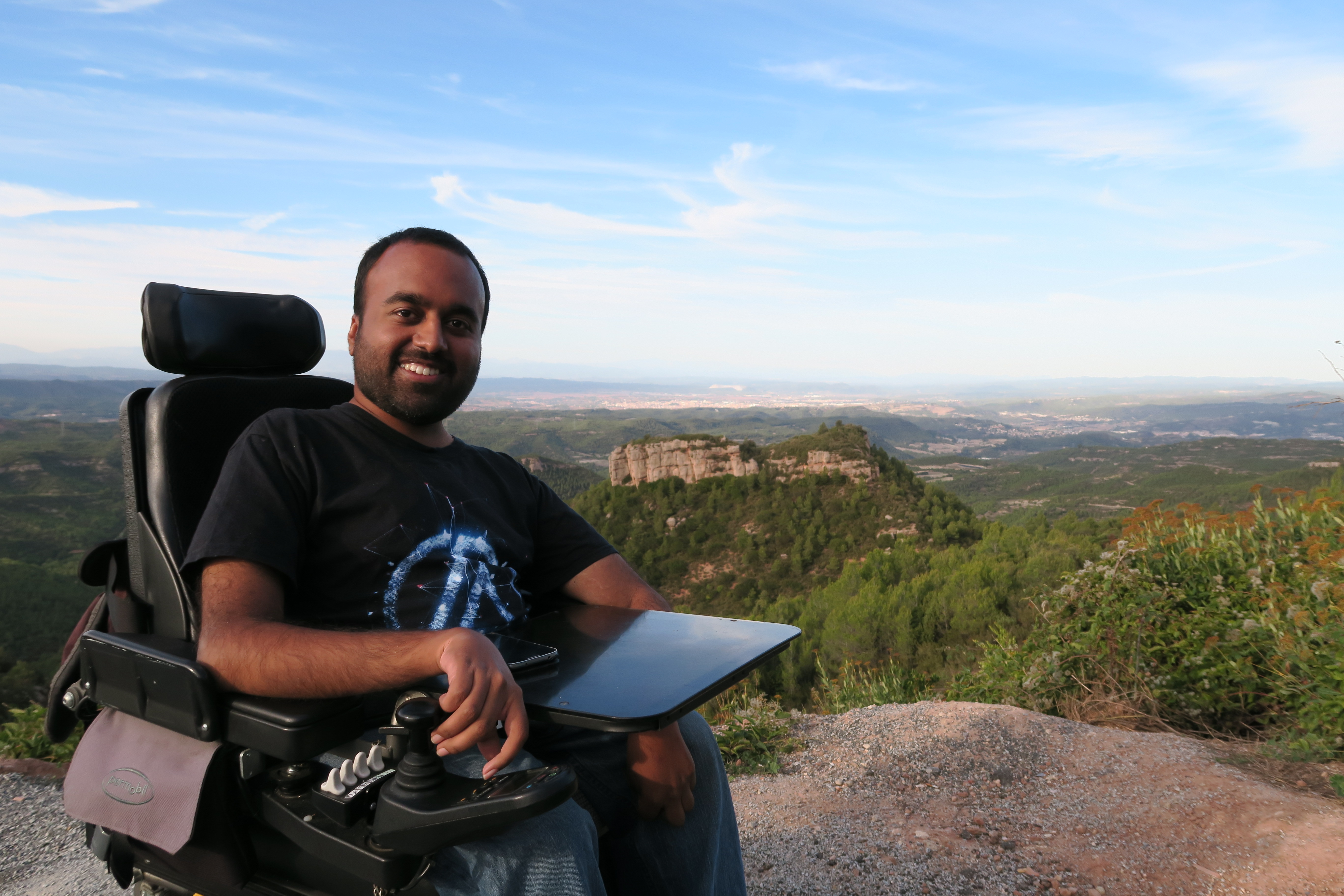 Man in wheelchair at the top of a mountain looking at the camera