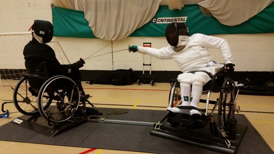 jonathan collins and his duelling partner playing wheelchair fencing in a sports hall