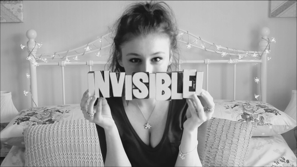 black and white image of woman sat on bed holding the words invisible i