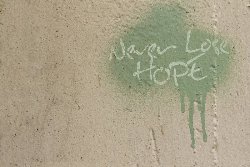 blank wall with green graffiti reading never lose hope