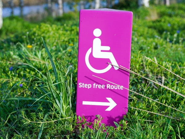 A pink sign in the grass it has a wheelchair symbol and says step free access with an arrow pointing to the right