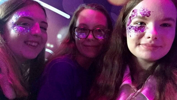 three girls in a selfie Its quite dark and they have pink glitter on their face