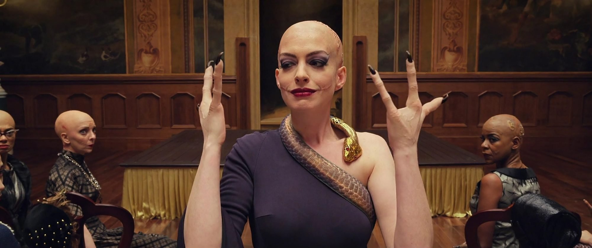 picture of anne hathaway as the grand high witch with three fingers on her hand
