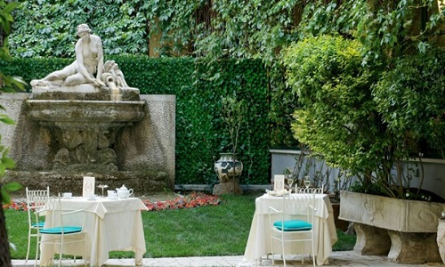 Hotel Quirinale garden with historic monument and table settings