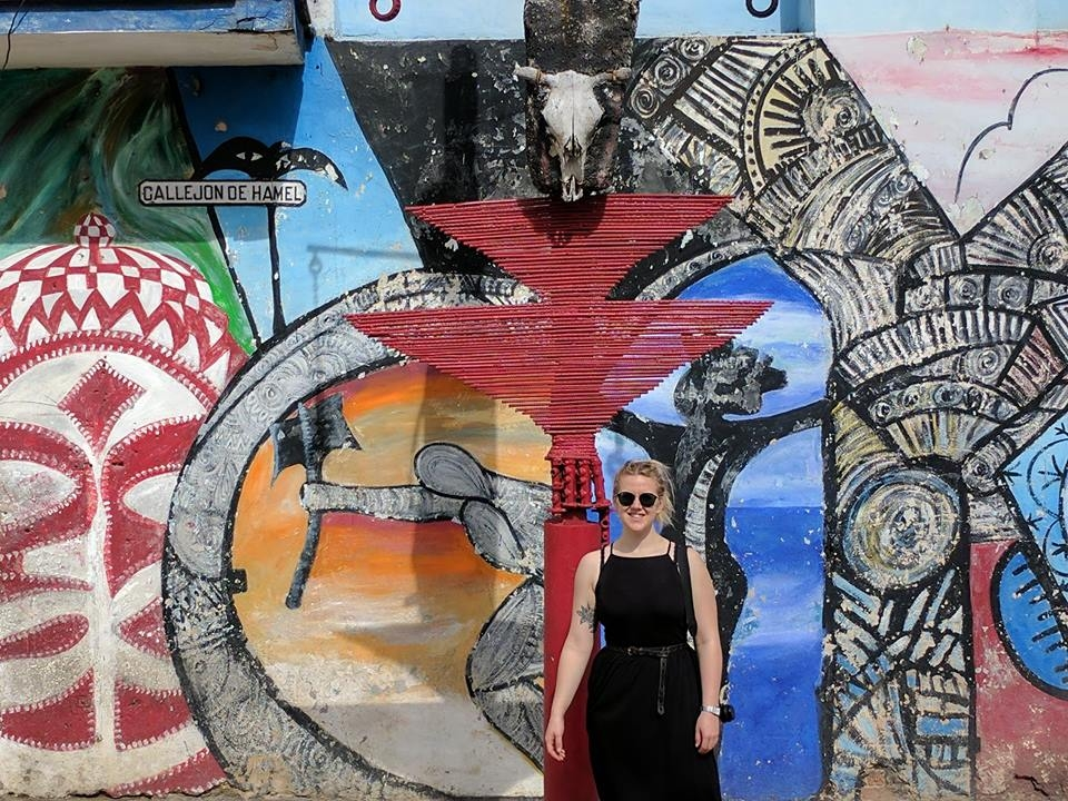 Young woman in a black dress in front of a wall of art