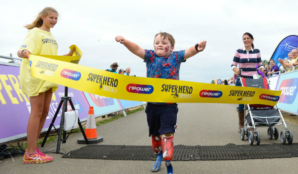 A young boy crossing the finish line at the Superhero Tri event