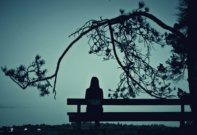 Girl sitting alone on park bench in twilight