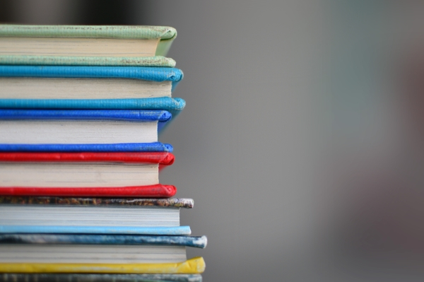 I pile of colourful books on the right hand side, with the background being blurred.