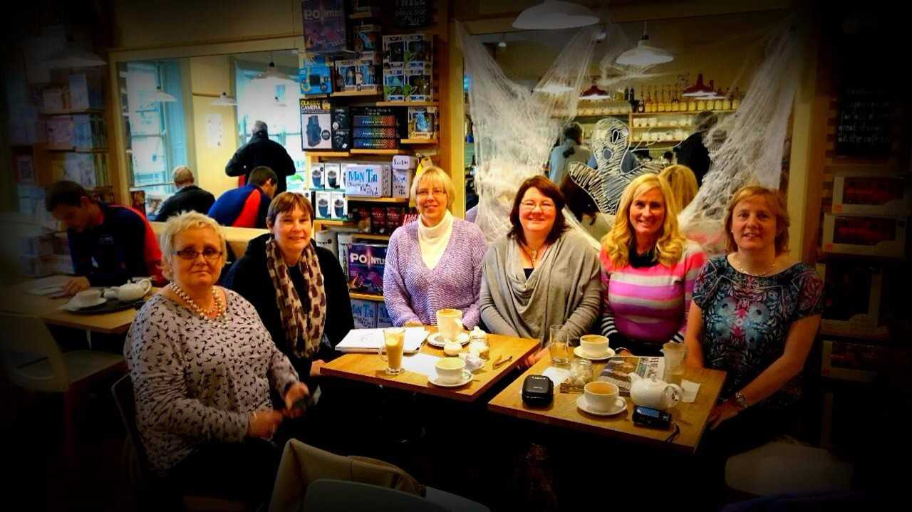 six women smiling at the camera whilst sitting around a large coffee table with newspapers teacups and various cakes on top of it