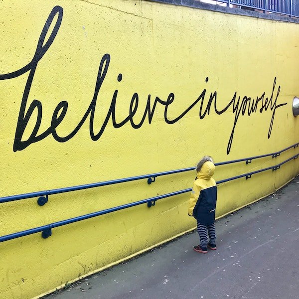 Photograph of a young boy looking at a yellow wall that has believe in yourself painted across it