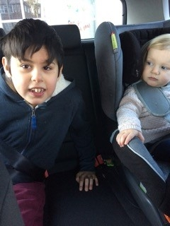 Young boy with blue zip up jacket smiling at camera, with young toddler in car seat on the right looking at him