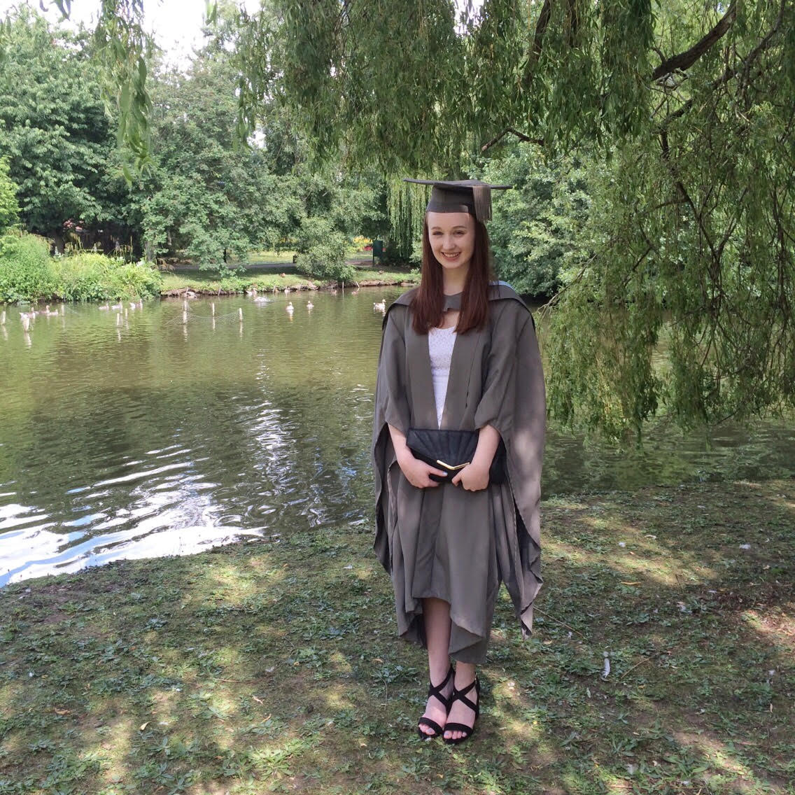 young woman wearing graduation cap and gown stood outdoors in front of trees and a lake