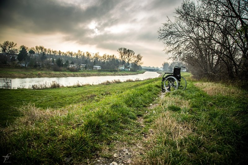 landscape image of an empty wheelchair with a river and green country hills in the background