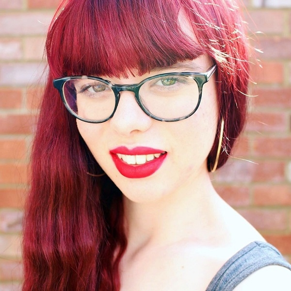 close up image of woman with red hair and glasses