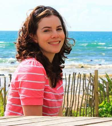 headshot of a woman with brown curly hair and wearing a pink top smiling at the camera with beach and ocean in the background