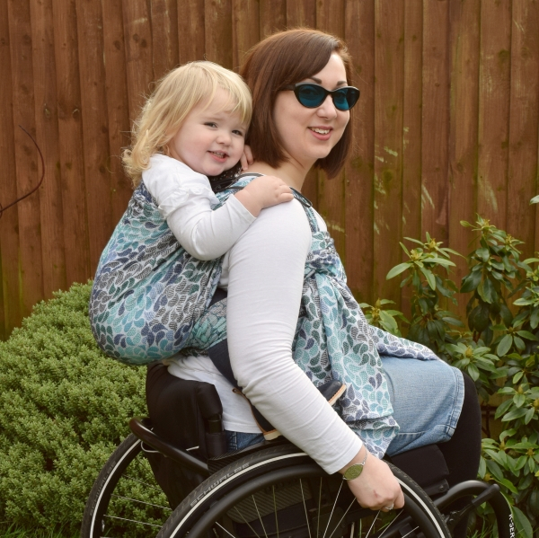 Tania is sat in a wheelchair with her daughter in a sling which is on her back