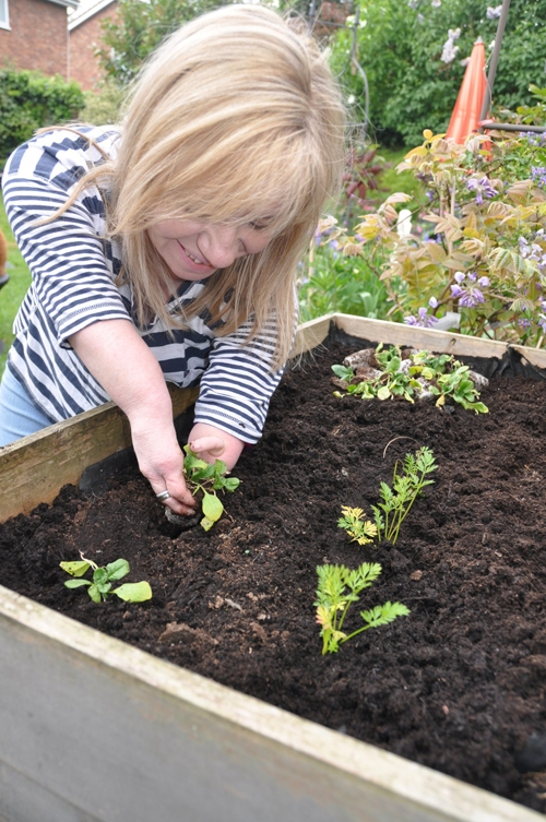 Niki smiling as she plants vegetables in her garden