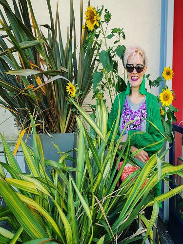 Imogen smiling wearing a bright green cardigan and surrounded by sunflowers and plants