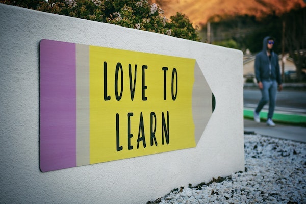 A wall sign with a pink and yellow pencil on that has love to learn printed on it