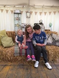 Three children - two girls and a boy - sitting on a sofa