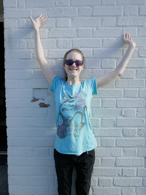 Jennifer smiling wearing purple Irlen lenses with her hands in the air