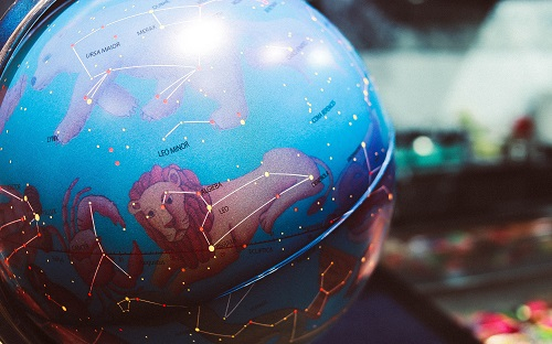 A globe with zodiac symbols on instead of countries lit up with fairy type lights