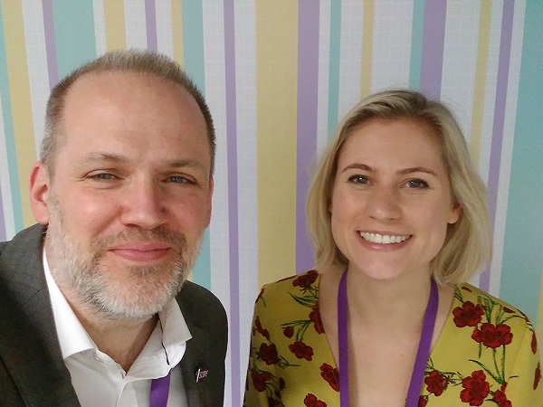 A man Ceri and a woman Krissie in front of a striped purple grey yellow and teal background