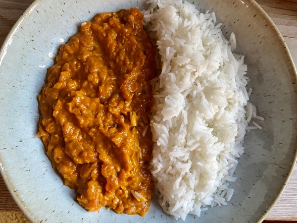 Circular bowl half with rice and half with red lentil dahl