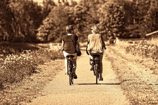 two women riding bikes outdoors
