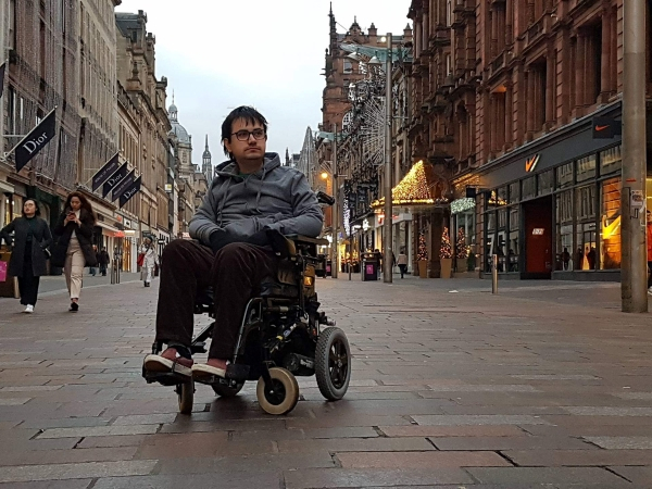 landscape picture of matthew in his powerchair looking into the distance