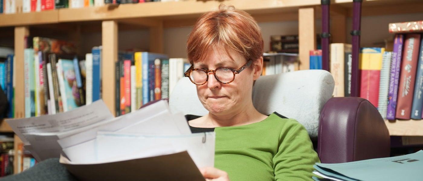 woman in glasses looking worried going through paperwork