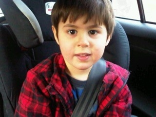 Young boy smiling at camera with his seatbelt on, wearing a red shirt