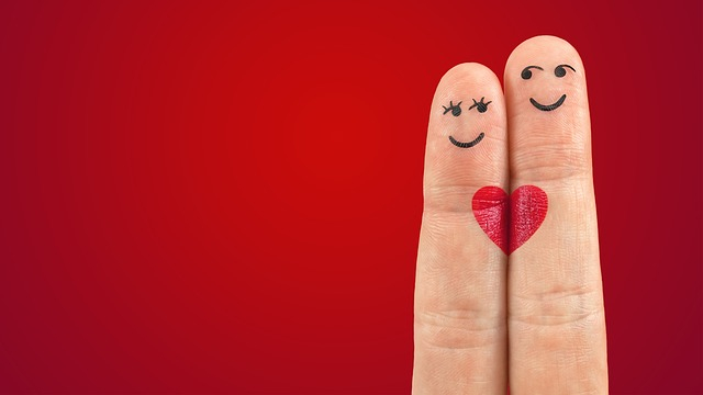 two fingers on a red background with a love heart drawn on them
