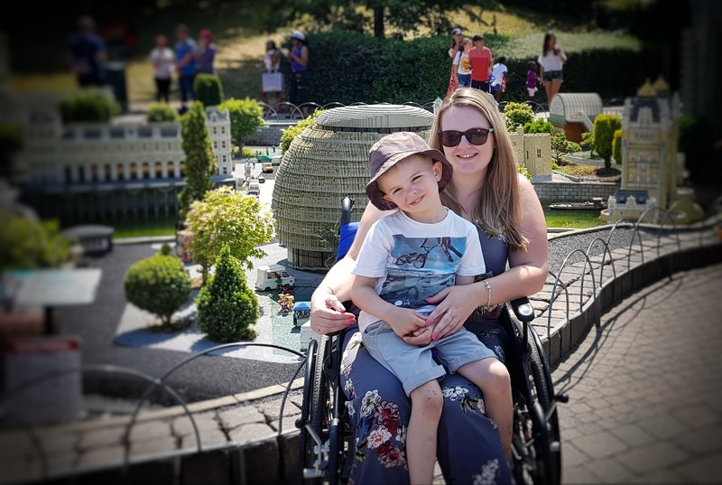 lucy wearing sunglasses sat in wheelchair with four year old son on her knee smiling at camera