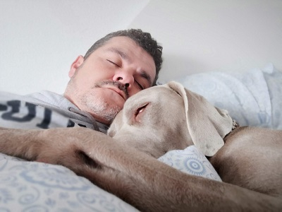 Man asleep in bed with his dog snuggled up to him