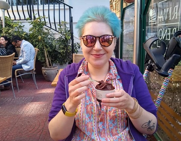 A woman eating ice cream outside at a cafe
