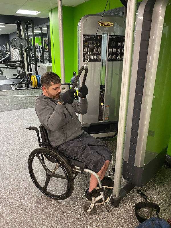 A gentleman in a wheelchair using a pulley weight machine