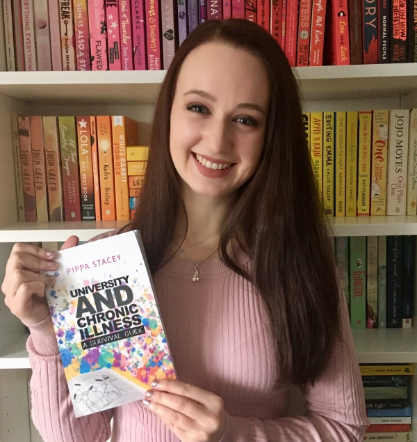 Pippa holding a copy of her book with a white book shelf full of books behind her