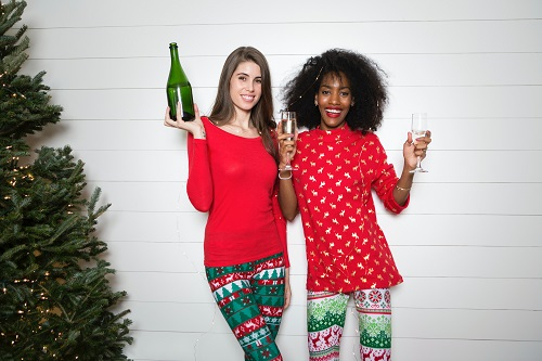 Two women in festive red clothes stood smiling holding wine glasses next to a Christmas tree