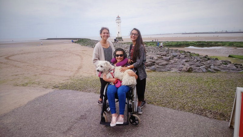 three young girls on a path in front of a beach youngest girl is in a wheelchair wearing sunglasses ear defenders and a neck-rest whilst holding a small white dog whilst two older girls stand either side of the wheelchair smiling