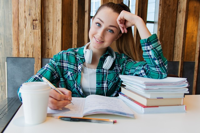 student wearing a green shirt smiling to camera and studying with a pile of books