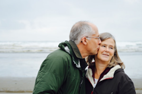 Elderly man kissing his partner stood on a beach with the sea in the background