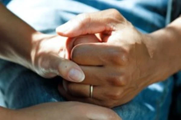 A photograph of one hand holding another another in a gesture of support