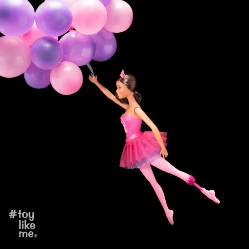 Barbie doll being pulled away by balloons