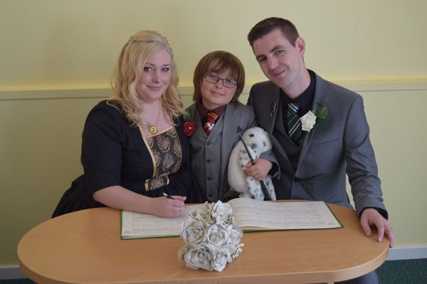 Charlotte with her son and husband signing a marriage register