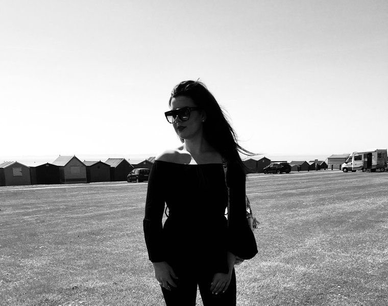 black and white image of long haired girl looking to the left and wearing sunglasses an off-shoulder top and jeans stood outside with vast fields in the background